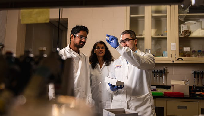 Biomolecular engineering professor Mark Blenner examines a test tube in the lab with a female professor and male student.