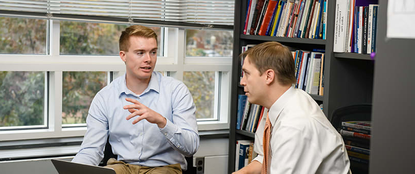 Political science major Dylan Erikson discusses a concept with his professor in a modern office setting.