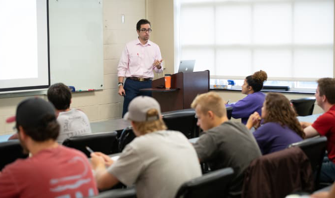 Male professor with glasses presents to a class of students sitting in rows in an academic building on campus.