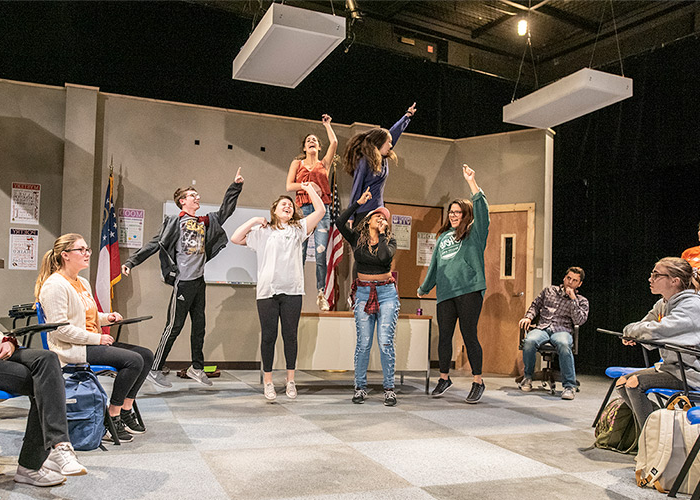 Six performing arts majors sing and jump in the air while on a set designed to emulate a classroom in the Brooks Center.