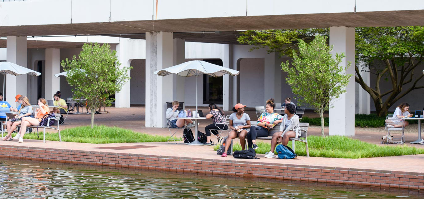 bet36体育 students sit at tables underneath library bridge beside the reflection pond.