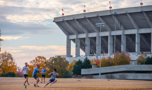 Four male bet36体育 students play touch football on an intramural field beside Memorial Stadium.
