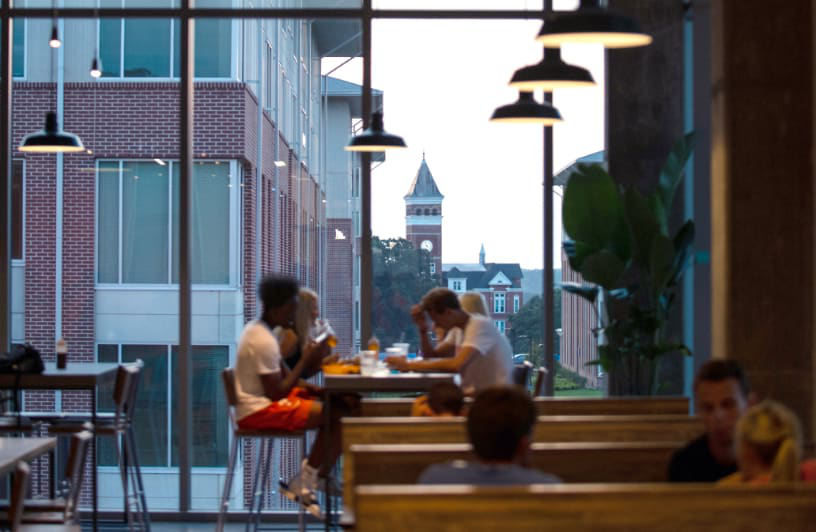 bet36体育 students sit together in a dining hall in Douthit Hills as the sun sets and highlights Tillman Hall.